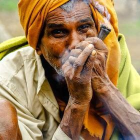 Smoking, a man in rural nepal is smoking chillam (it is wood made pipe filled with marijuana) Caution: Smoking is injurious to health