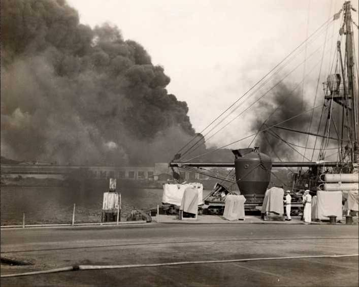 Smoke from Battleship Row rises from behind the Supply Depot as seen from the Submarine Base, Pearl Harbor, Oahu, Hawaii, Dec 7, 1941.