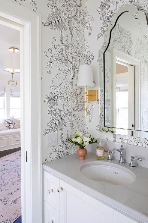 Sweet black and white kids' bathroom is clad in beautiful black and white wallpaper lit by Worlds Away Molly Gold Leafed Wall Sconces mounted flanking an Allen + Roth Hovan Arch Frameless Mirror.