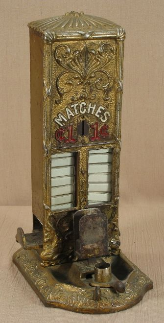 """Northwestern Sellem. Northwestern Corporation, Morris, IL, c. 1912, 13 1/2"""". Cigar cutter and match box holder. Was used in fine hotels. """"The top, front, and base are art noveau cast iron."""" Vending machine. Small Vintage Vending"""