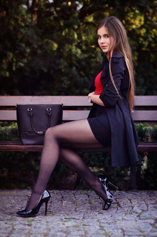 Czarny trencz, czerwony top z golfem, ołówkowa spódniczka i czarne rajstopy