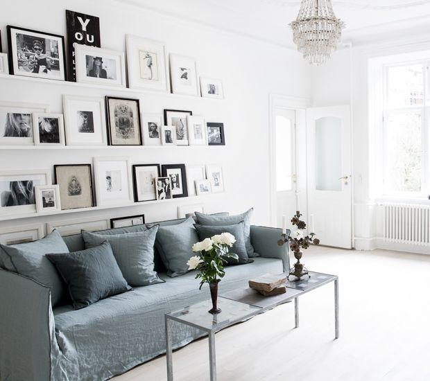 Et miks af enkle, stilrene møbler, personlige fotografer og hvide flader skaber en rolig atmosfære i stuen.