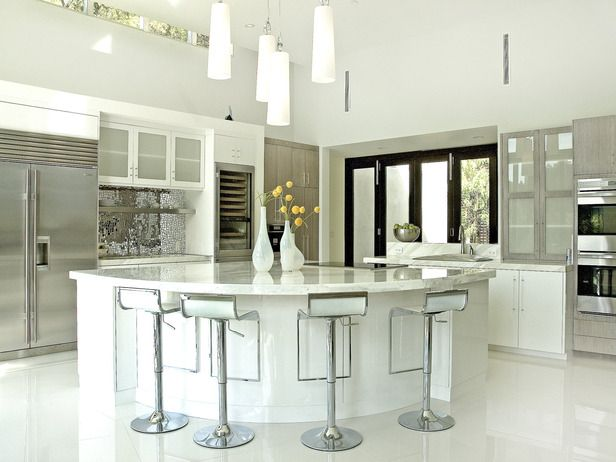 Cool and Glamorous Calacatta Gold countertops — an Italian white marble with gray and gold veins — set the tone for this contemporary kitchen. Designer Erinn Valencich took a classic white palette, warmed it by marrying white lacquer and gray-stained oak cabinets, and added a retro touch with a mirrored mosaic tile backsplash. Photo courtesy of Erinn Valencich