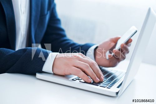 Businessman using laptop and mobile phone