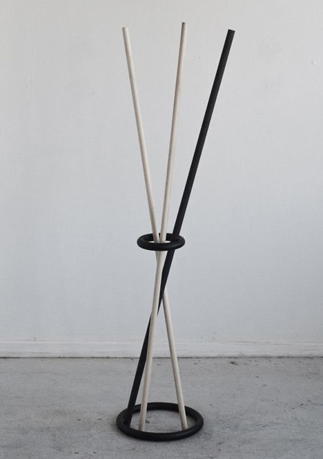 Poke Stand. This coat stand by Stockholm designer Kyuhyung Cho appears to defy gravity, with a hovering metal ring keeping four diagonal sticks from crashing to the ground. Additional wooden poles can be slotted through the ring so garments and accessories hang from the ends.