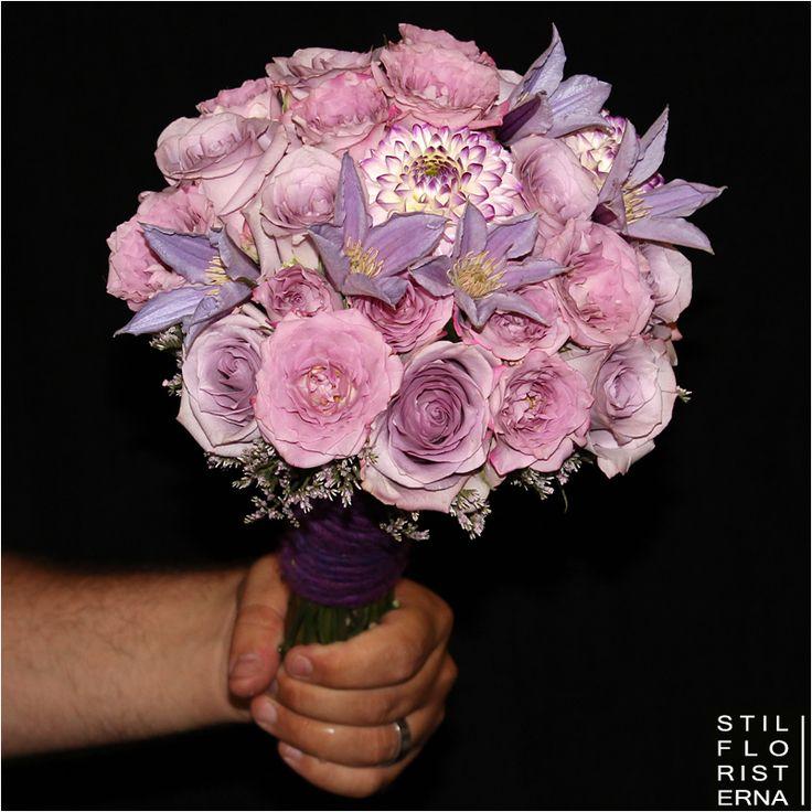 Handbunden kompakt brudbukett i ljusa lila toner, med lila rosor. dahlior och klematis.