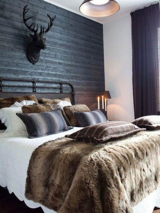 Masculine bedroom decor with faux fur pillows and throw blanket, brown and gray wool throw pillows, dark gray painted wall, mounted deer bust on the wall, iron bed frame, dark gray curtains, and crisp white sheets for contrast.