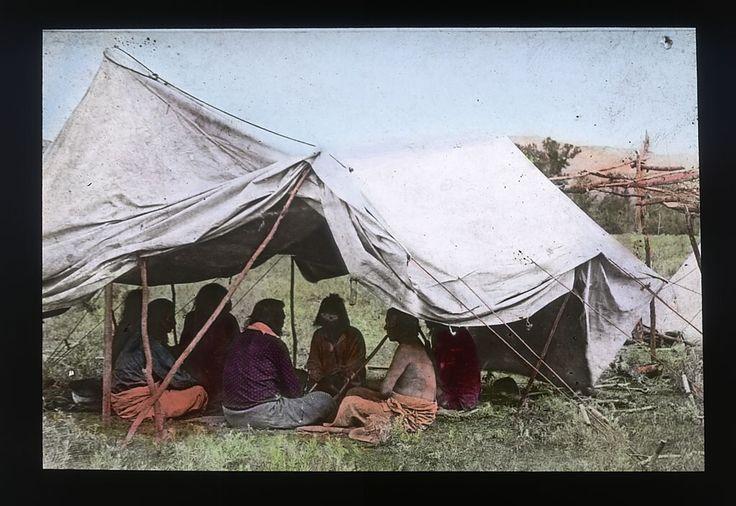Группа из семи человек под тентом, Кроу.  Father Peter Paul Prando.  National Anthropological Archives, Smithsonian Institution.