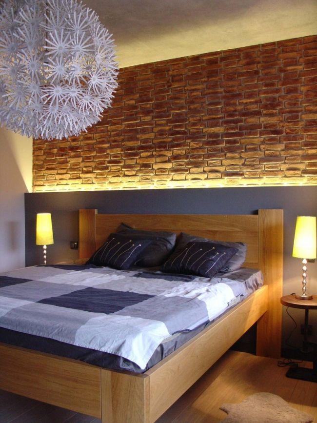 un lit en bois et un papier peint effet briques dans la chambre à coucher