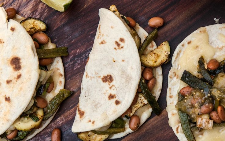 A healthy vegetarian fajitas recipe, with green onions, zucchini, pinto beans, and poblano peppers.