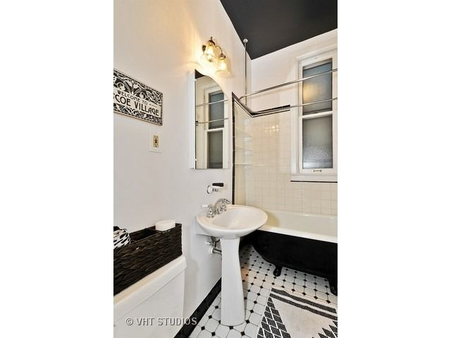 Black and white vintage bathroom with black bathtub accent | 3334 North Hamilton Avenue, Chicago, IL