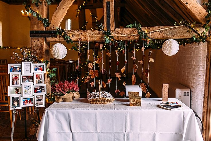 Leaf garlands, lanterns, dried flower confetti, a jingo guest book, wooden handmade card holder and pictures of the wedding party - great wedding decor! Photo by Benjamin Stuart Photography #weddingphotography #wedingideas #barnwedding #diywedding #ceremonydecor