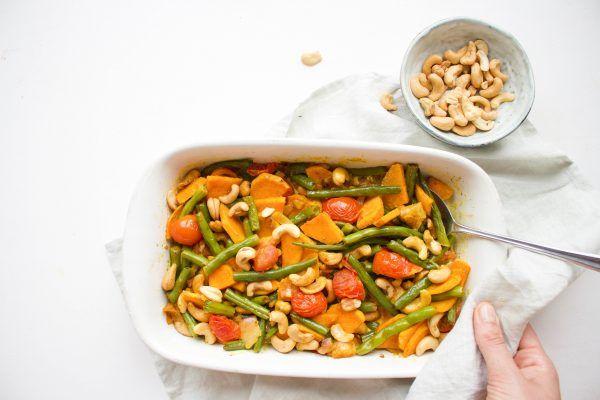 Een heerlijke, gezonde en plantaardige ovenschotel van zoete aardappel, sperziebonen, tomaten, cashewnoten en veel kruiden!