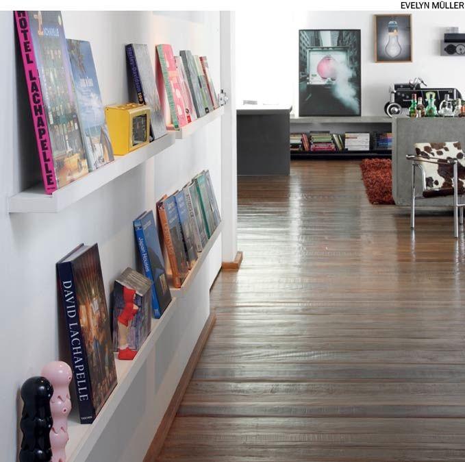 Canaletas de madeira com pouca profundidade são excelentes para exibir quadros, livros e objetos de decoração, como na casa da arquiteta Juliana Grave. A vantagem em relação aos pregos é poder mudar as obras de posição.