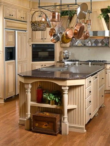 This classic kitchen features dark granite top central island with a shelf, several drawers and cabinets.