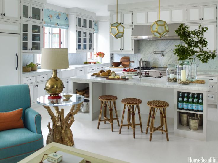 Traditional yet playful, the kitchen features 1920s French brass pendants from Blend Interiors, Carrara marble counters, rattan stools by TK Collections, and a Wolf range. The sink fittings are by Hans grohe. The cabinets are painted in White, with trim in Balboa Mist and wood floors in Silver Satin, all by Benjamin Moore.