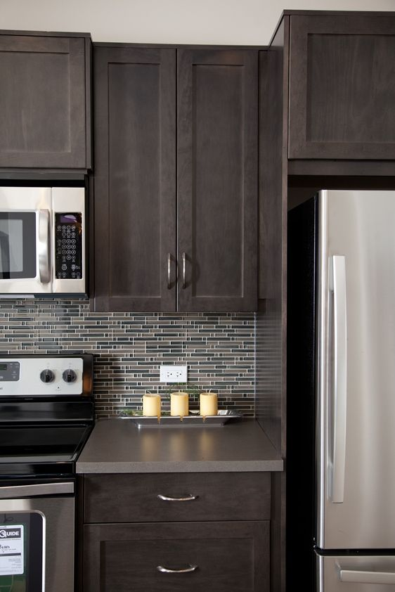 kitchen brown maple shakerstyle cabinets stainless steel microwave stove and fridge with glass mosaic tile backsplash at prospect rise calgary townhomes