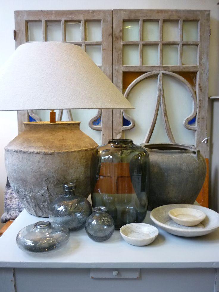 Interieur in grijs; oud kaarttafeltje, art deco deuren, kruik als lampvoet, potten, vazen, schalen