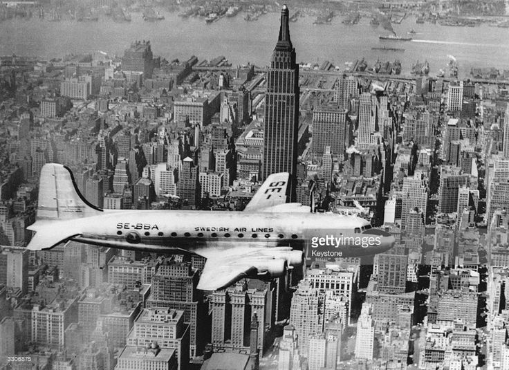 The first Swedish airline passenger plane, a DC-4, flies up the East River, New York, en route to la Guardia Airport. The Empire State Building can be seen in the background.