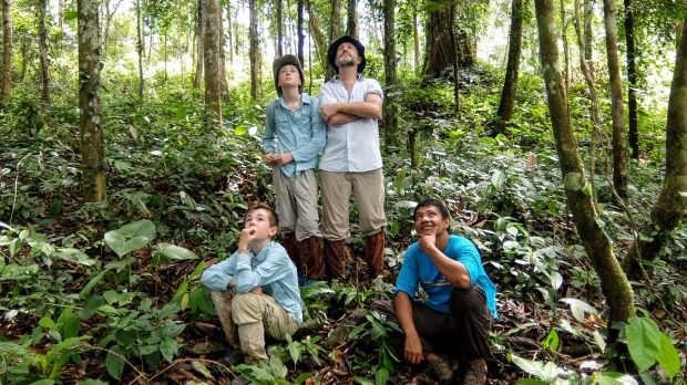 Seeing Orangutans in the wild with jungle guide Udin. Pictured, clockwise from back left, Tom, Chris, Udin and Kit.Photo: Penny Stephens