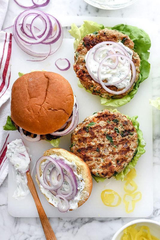 Greek Turkey Burgers with Tzatziki Sauce are packed with fresh spinach, sun-dried tomatoes, oregano and feta cheese for a healthy Mediterranean version for hamburger fans   foodiecrush.com