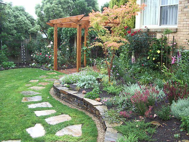 Garden with Castlemaine slate stepping stones, stone wall and Acer palmatum 'Senkaki' set amongst mixed plantings.