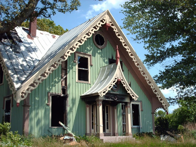 Carpenter Gothic house with muted blue-green board and batten siding, cream gingerbread trim, burgundy accents and a standing seam metal roof. - source: Vertext