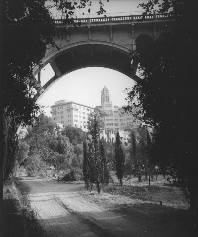 (ca. 1937) - This view of the Vista del Arroyo Hotel in Pasadena shot through the Colorado Street bridge captures a dirt path lined with Cypress trees leading through the lush arroyo.  It is now the Richard H. Chambers U.S Court of Appeals, Pasadena, CA
