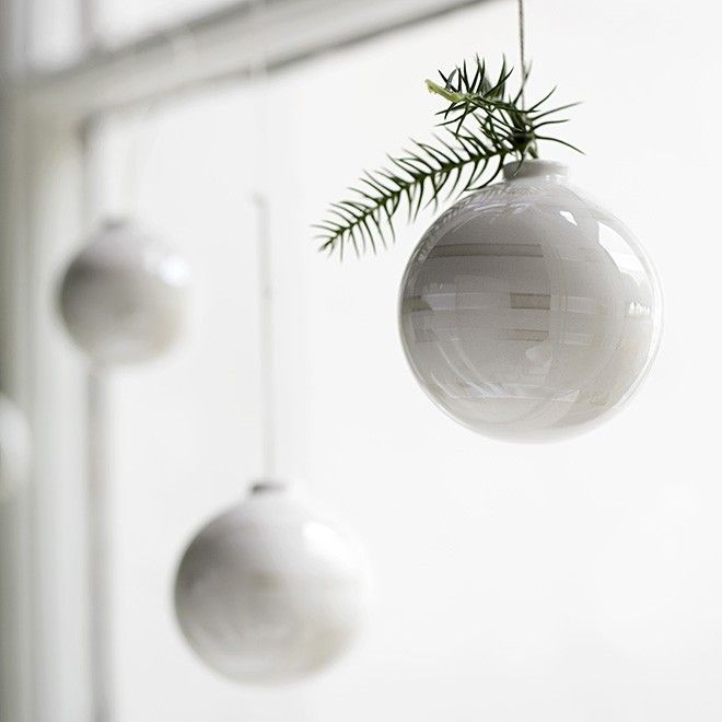 This year, decorate your home with the stylish Omaggio Christmas baubles and their mother-of-pearl stripes. The hand-painted mother-of-pearl stripes discreetly reflect the rays of light and add a new and delicate lightness to the design. Whether decorating a dark green Christmas tree or hanging in windows as ornaments throughout the home, they glimmer like tiny, vibrant snowflakes at this dark, cosy time of year.