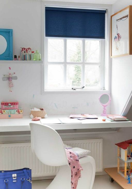 Onder het raam van de dakkapel en boven de verwarming dient een plank als bureau.Op die manier is goed gebruik gemaakt van alle ruimte in de kamer.