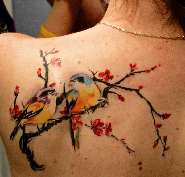 A very pretty looking tattoo of two birds perched on a branch with red flowers. The style which the birds are drawn is also very attractive and pleasing to the eye.