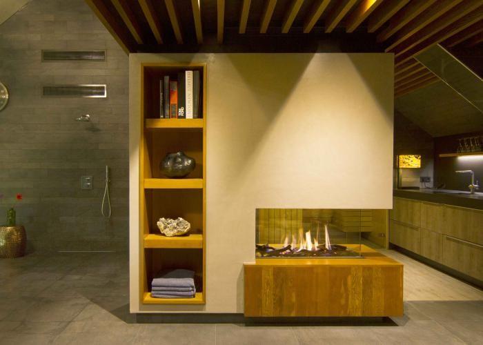 Moderne inbouw haard in de relaxruimte van de  woning, in de tussenmuur met opbergvakken   Profires partner Jos Harm · inspiratie voor sfeerverwarming