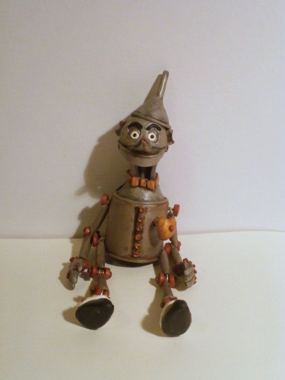 <Polymer clay tin man miniature brooch/pendant> What I would do differently: I would make it smaller, better legs to arms ratio, his teeth don't show bc the chin support in the oven was too high. He is spooky but nice and a poser!
