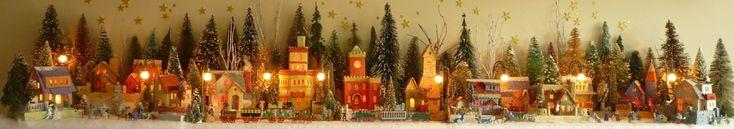 Antique Christmas cardboard house putz (village) on fireplace mantel at night (105K)