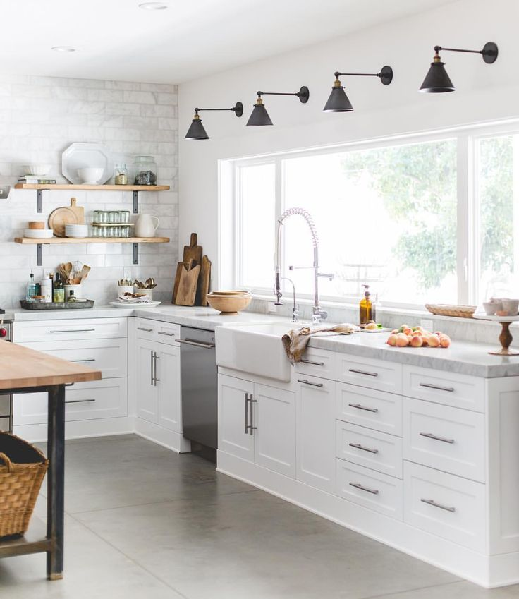 Chic white kitchen with marble counters. Love the black wall sconces in a row above the counter.