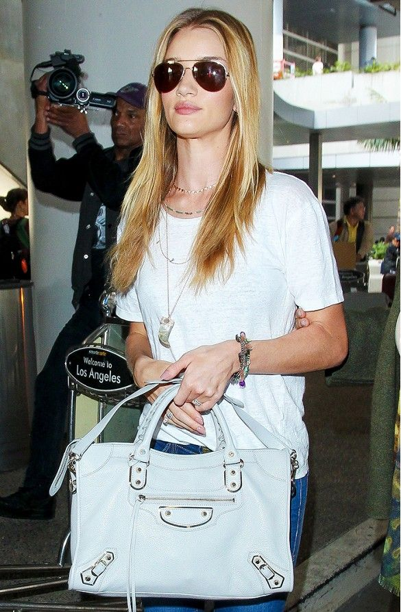 Rosie Huntington-Whiteley wears a white t-shirt, jeans, Balenciaga bag, and Jacquie Aiche necklaces