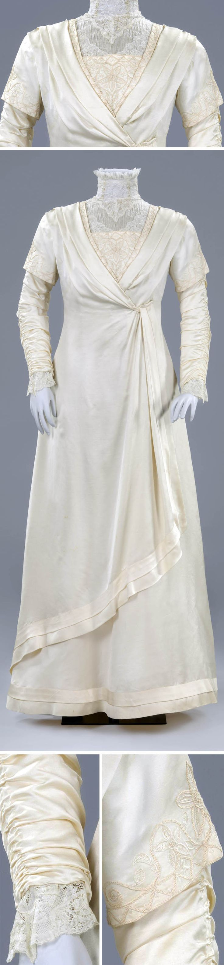 """Wedding dress, the Netherlands, in or before 1909. """"Robe Tanagréenne,"""" after terracotta figurines from Greek town of Tanagra, introduced in Paris in 1908. White satin with gaze de soie, 18th century Mechlin bobbin lace, and passementerie. One-piece gown with petticoat and matching glacé leather shoes. Front closure hidden under tunic-shaped flap. Rijksmuseum"""