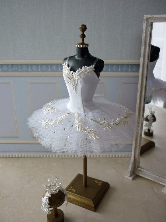 本物のバレエ衣装チュチュを部屋に飾り毎日眺めていたい、そんな思いから作り始めました。1/6ドールサイズのトルソーに合わせて作ったミニチュアのチュチュです。「白鳥の湖」のオデットを踊るバレリーナをイメージして、白色のシャンタン生地とチュールに白色のレースと銀色のビーズ、スワロフスキーのストーン等で飾り付けをしています。肩紐は透明ゴムです。スカート部分も3段仕立てで本格的作りになっています。トルソーの高さ 約25センチスカートの巾 約14センチバービーに着せることもできます。(バービーには胸周りに少し余裕があります。)できるだけ本物のチュチュをミニチュアサイズで再現できるように、実際のチュチュの作り方を参考にパターンおこしから細部までこだわって作りました。トルソーに着せやすくするために背中は全開きになっています。トルソーに着せるため本物のクラシックチュチュ(短いスカートのチュチュ)に付いているツンと呼ばれるパンツ部分が付けられないので、スカート部分はロマンチックチュチュ(長いスカートのチュチュ)の作り方を参考に仕立てています。トルソーは市販のものをお洒落にカスタマイズしたも...