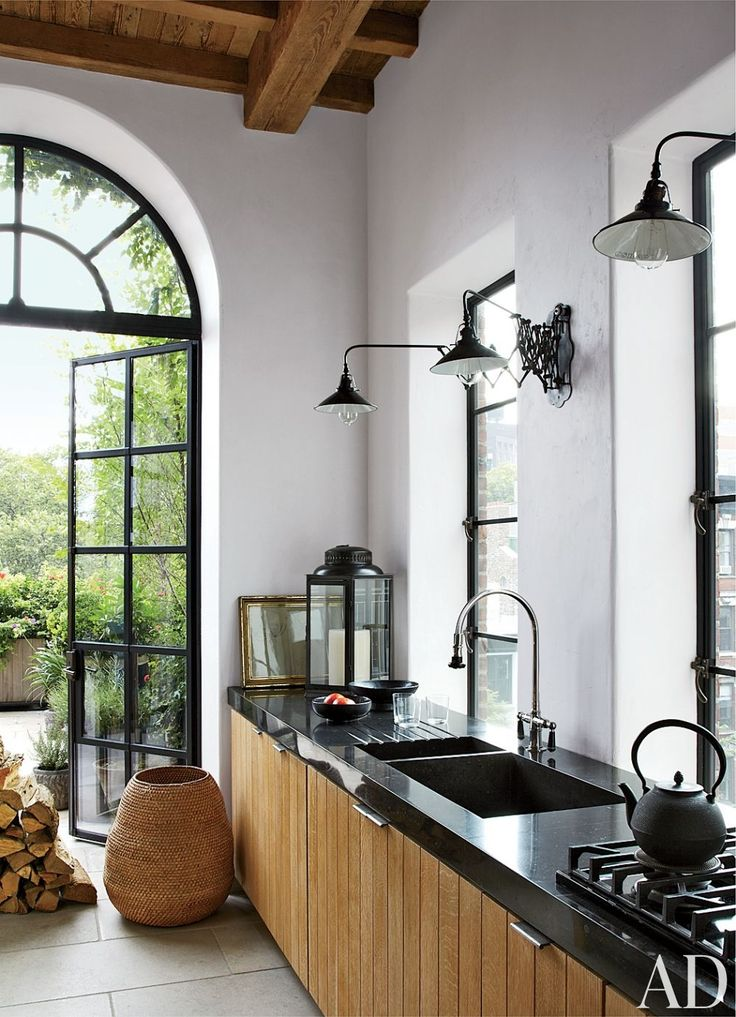 Industrial light fixtures and bluestone countertops complement white-oak cabinetry in a Manhattan kitchen; the pulls are by E. R. Butler. Rustic Kitchen by Alfredo Paredes and Michael Neumann Architecture in New York, New York
