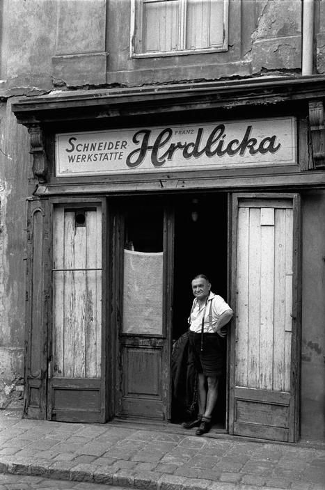 by Erich Lessing  AUSTRIA. Vienna. 1954. Life in post-war Vienna: A tailor in traditional leather shorts stands in front of his shop. Shop windows are still boarded up after war damage.