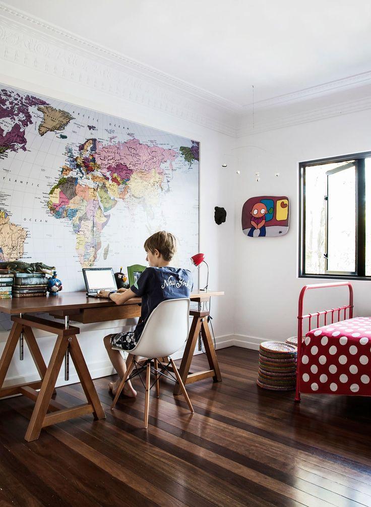 Kids room: large world map wallpaper art in white frame, polished timber floorboards, wooden trestle desk