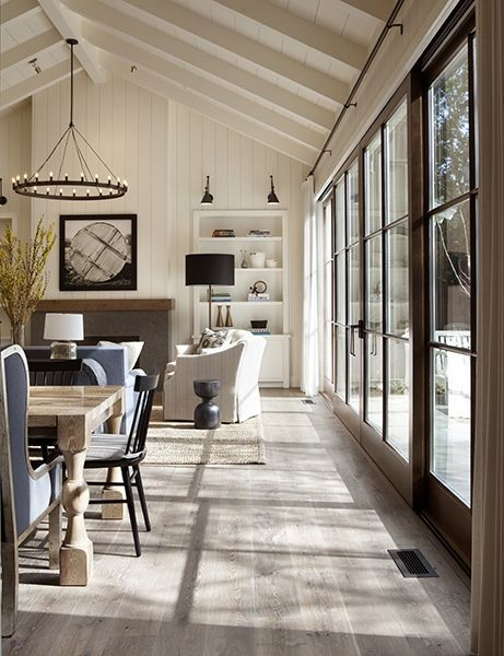 Living Room decor - rustic farmhouse style. Painted open beam ceilings, slipcovered sofas, light colored hardwood floors, sliding / folding doors, round candelabra chandelier, built in bookshelves on either side of fireplace, rustic dining room table.