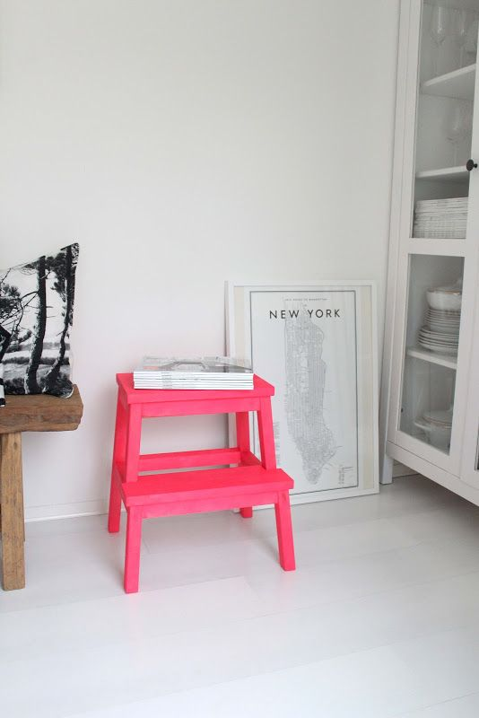 Neon pink stool with a white floorboard and white walls.
