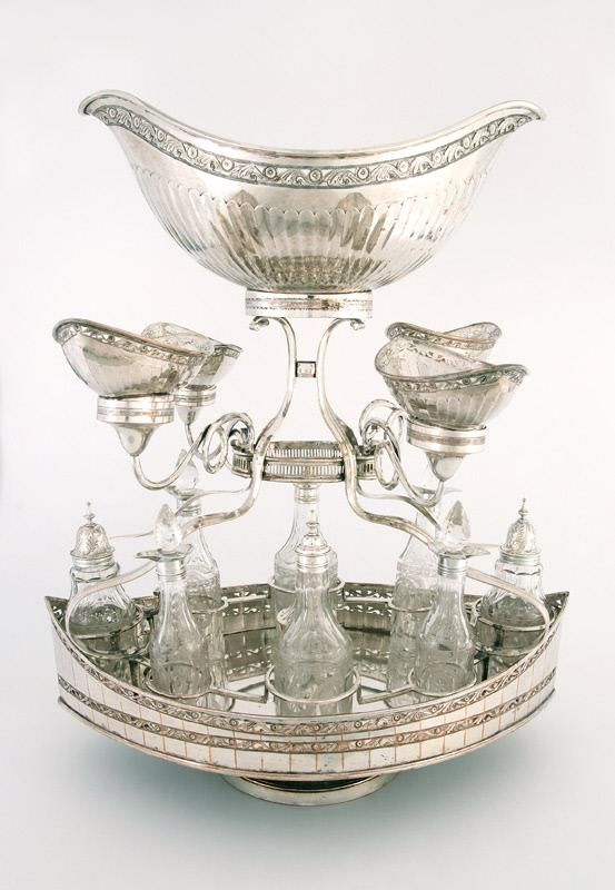 Epergne 1760-1800: These were luxurious centerpieces used for social occasions in wealthier households. They traditionally held fruit or sweetmeats. The surrounding bottles were used for condiments. They were impractical because they were delicate and difficult to clean.