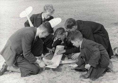 Jonge jongens en jong meisjes.  Groepje jongens op het strand met model   (zweef) vliegtuigen. De heren zijn gekleed in winterjassen en een plusfours   kostuum met geruite wollen kousen. 23 mei 1941, plaats onbekend.