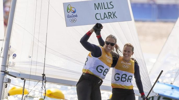 Hannah Mills and Saskia Clark celebrate after winning the gold medal in the women's two-person dinghy 470 sailing event