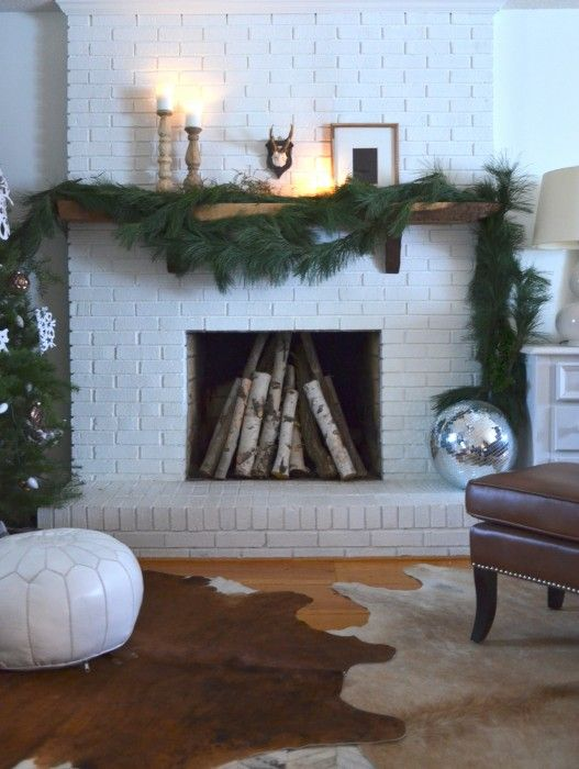 Of course, your fireplace doesn't have a raised hearth or go all the way up the wall like this one, but this is still a good look...paint bricks white and add a rustic, live-edge mantel.