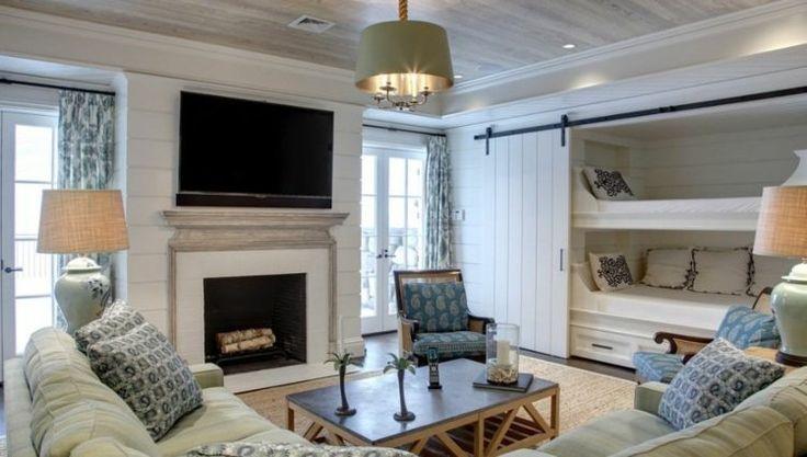 salle de séjour de style chalet de montagne aménagée avec un lit superposé, porte de grange coulissante, cheminée et canapé rembourré