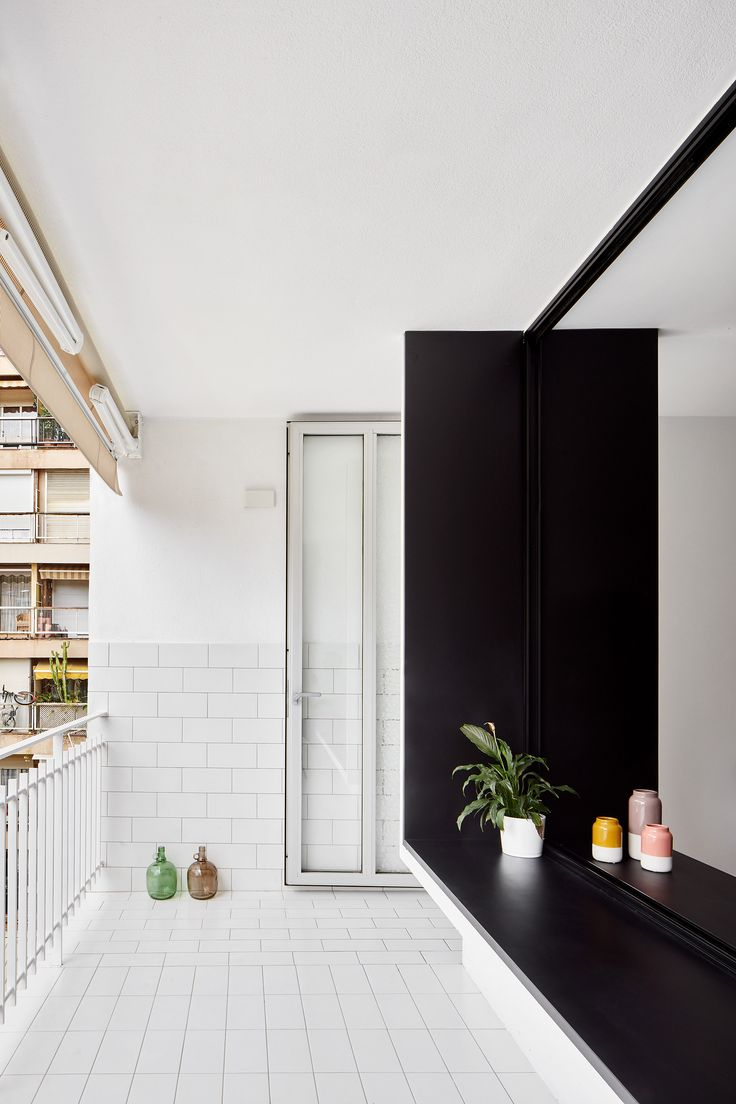 The lounge is fronted by a large window that overlooks a white-tiled balcony – the window's chunky ledge also offers inhabitants an alternative place to sit or display their possessions.