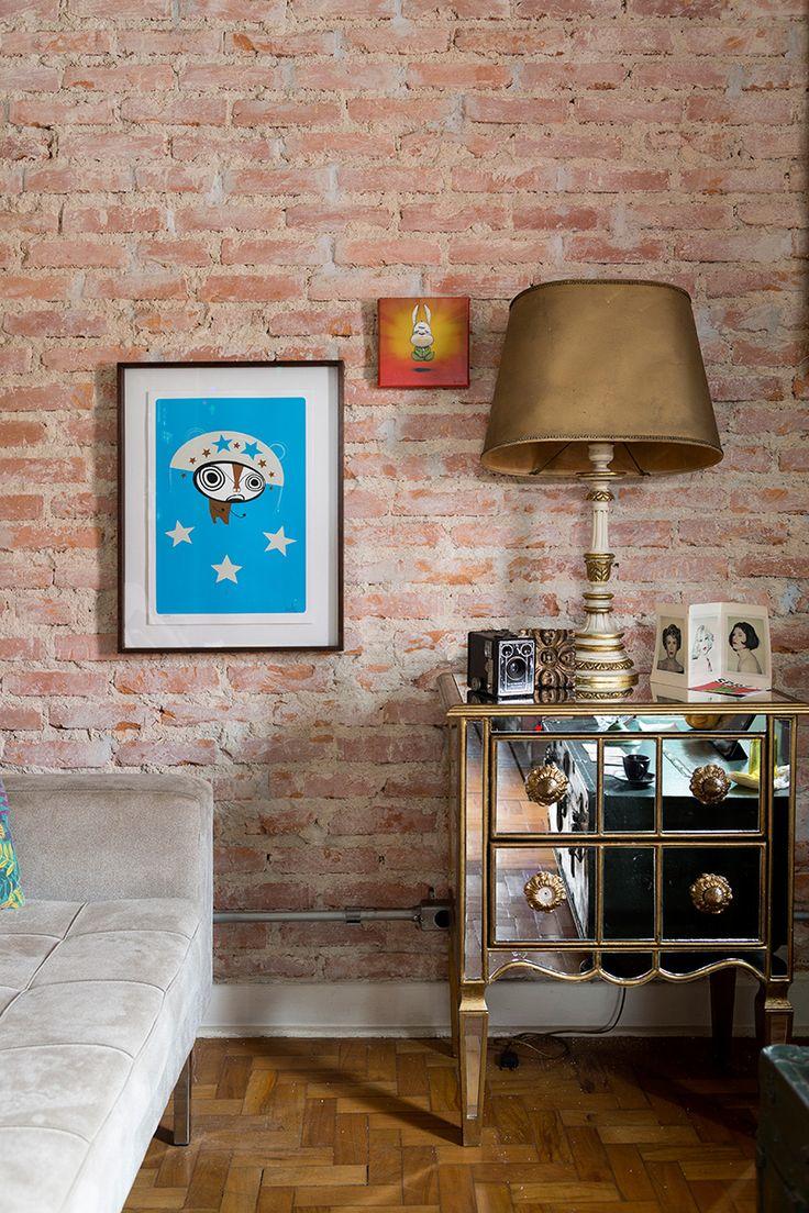 Casa pequena, casa charmosa, detalhes da decoração, parede de tijolinhos, abajur dourado, quadros.